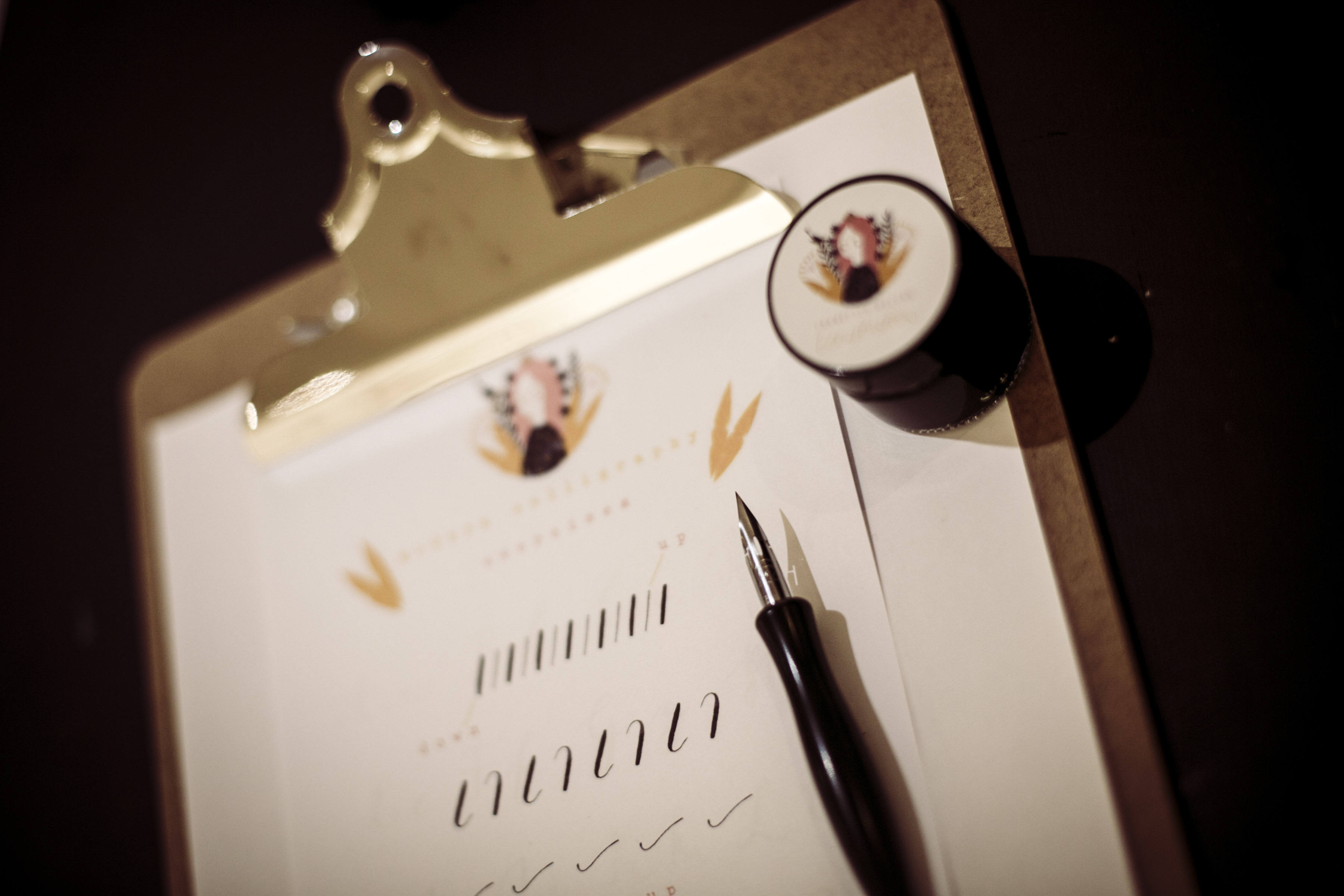Francesca McLean Introduction to Modern Calligraphy image showing pen, ink and clipboard with writing